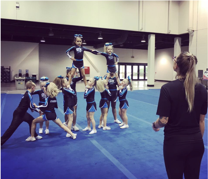 trainer helping cheerleaders into a pyramid