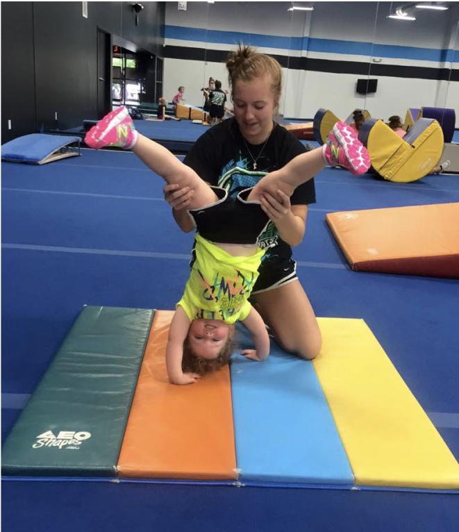 trainer helping preschooler do a handstand