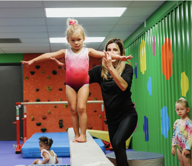 young gymnast on balance beam with trainer assisting