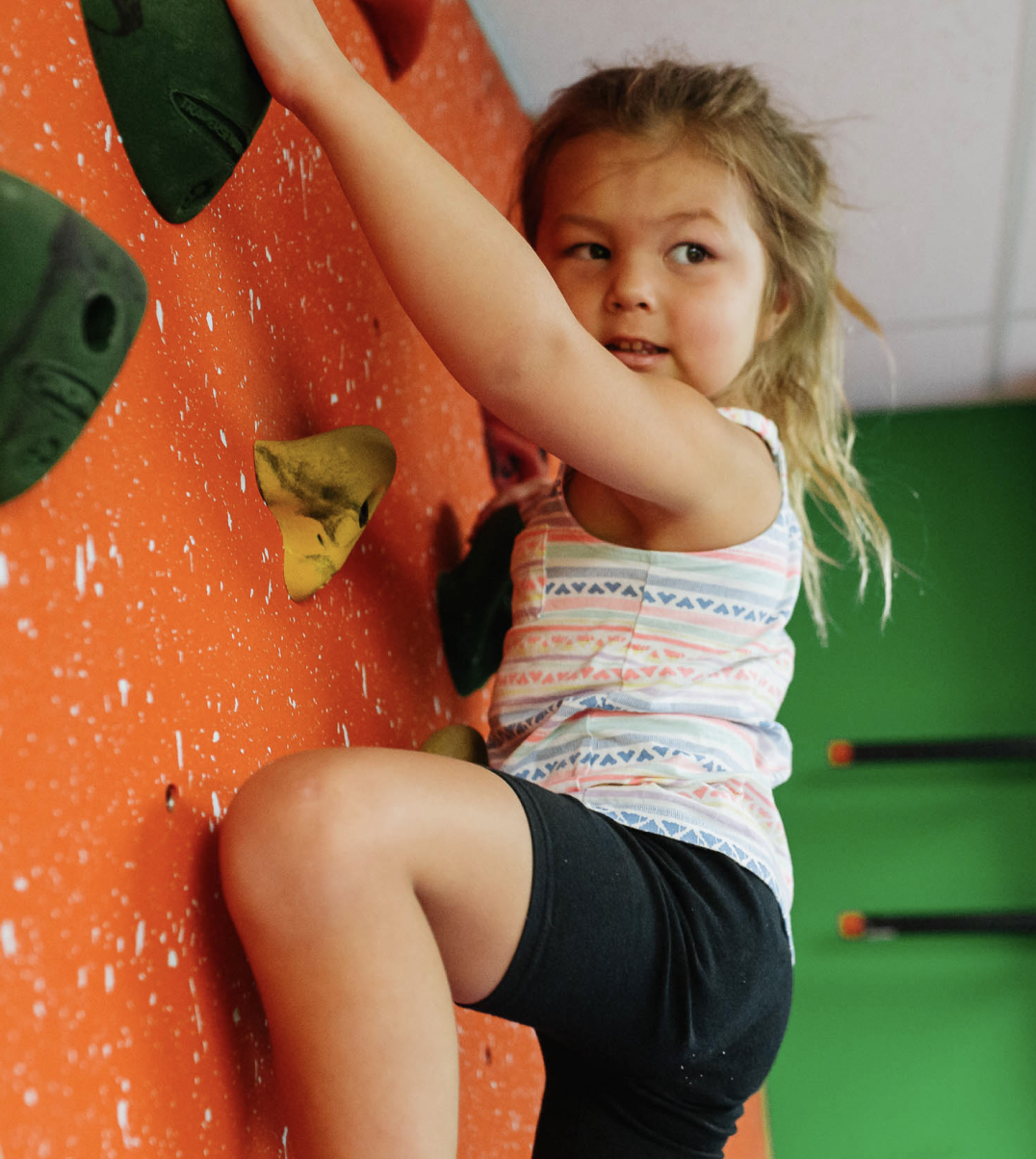 toddler playing on rock wall