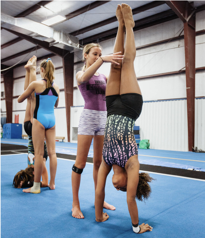 gymnasts practicing handstands