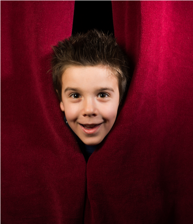 young boy behind a red curtain