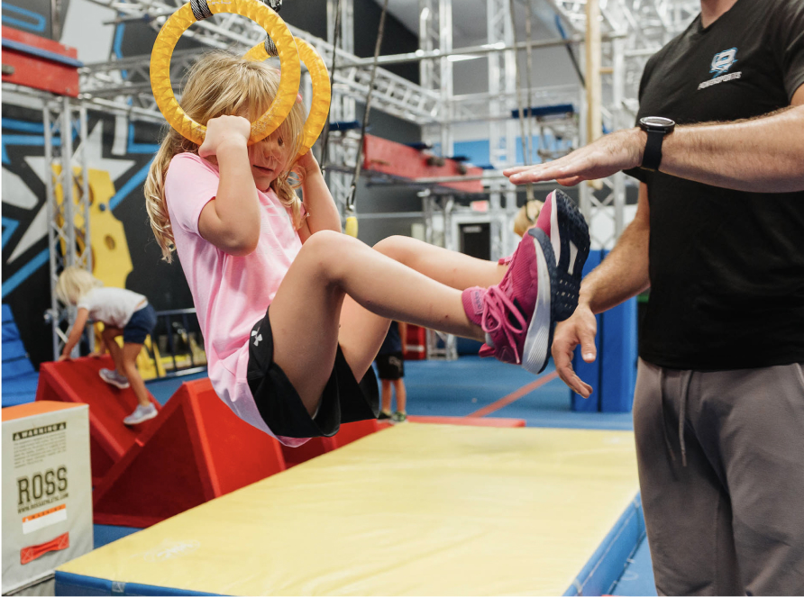preschooler using rings on an obstacle course