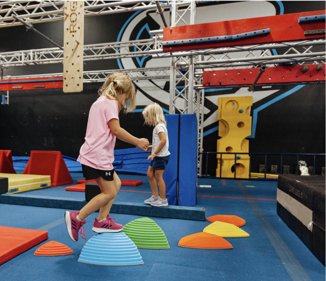 kids balancing on ninja warrior course obstacles