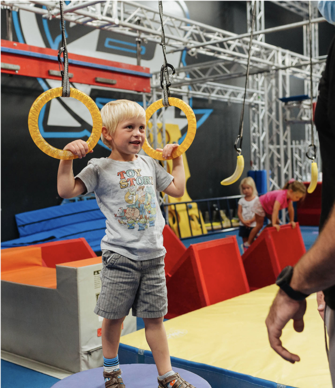 preschooler using rings on ninja warrior course